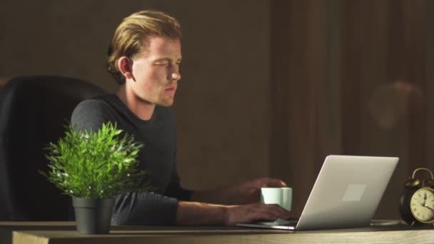 junger blonder Geschäftsmann arbeitet im modernen Büro am Notizbuch und trinkt Tee im bequemen Ledersessel.