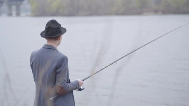 Mladý rybář v bundě a čepice s okrajem v časných ranních hodinách rybaření v řece nedaleko města. Rybářská prut a naviják. Fly rybář na řece
