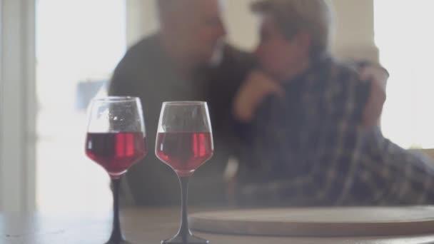 Zwei Gläser Rotwein und im Hintergrund die Silhouette eines älteren Ehepaares. Mann hält mit Liebe Frau und küsst ihre Nase.