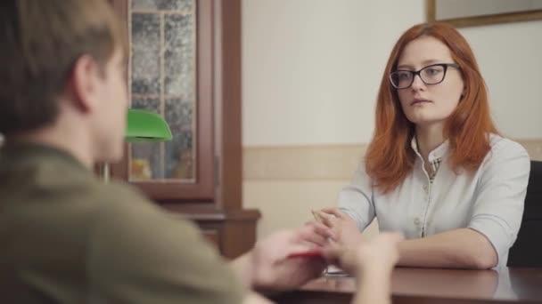 Portré női pszichológusról, aki épp a betegével tárgyal. Gyönyörű vörös hajú női pszichológus szemüveggel. Mentális egészség.