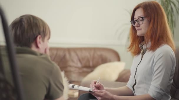 Pohled zezadu na mladého muže sedícího na lůžku v kanceláři psychologa, jak jí vypráví o svých problémech. Krásná žena psycholog poradenství její dospívající pacient píše poznámky do notebooku