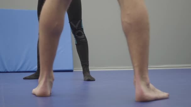 Close up of feet of the man and woman having training in the gym. Warming up before sparring. Male and female legs turning on the toes. The man is barefoot, the lady is in socks