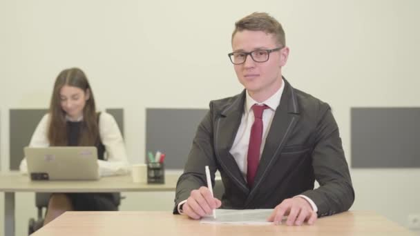 video of Confident young male manager in suit sitting at desk in foreground looking in camera. Attractive young woman in formal wear working with laptop on background