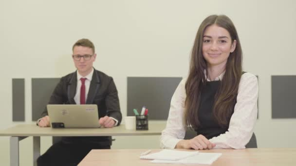 video of Confident young male and female managers in formal wear sitting at desks in office, showing thumbs up