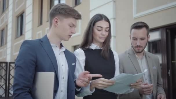 Young woman and two men in formal wear walking on  terrace discussing project, video