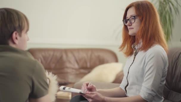 Mladý muž sedí na lůžku v kanceláři psychologa a vypráví jí o svých problémech. Krásná žena psycholog poradenství její dospívající pacient píše poznámky do notebooku