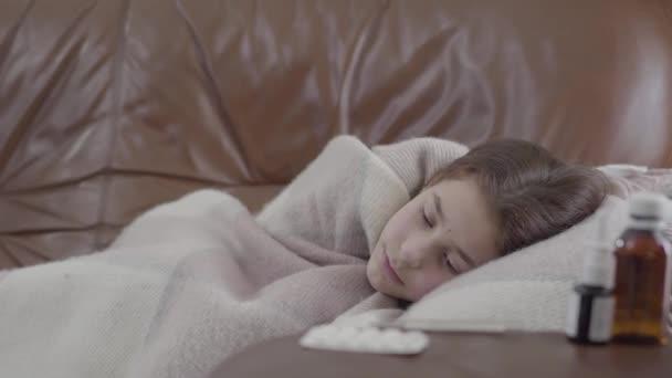 Zu Hause auf dem Sofa liegend, mit einer Decke bedeckt, ist sie kalt. Nasenspray, Tabletten und Sirup auf dem Tisch im Vordergrund. Gesundheitskonzept. Kamera bewegt sich nach links