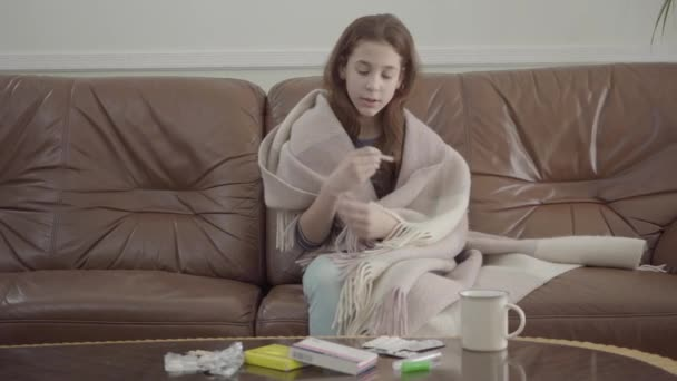 Caucasian girl sitting in leather sofa, tablets, pills and cup on the table. girl looking at thermometer, video