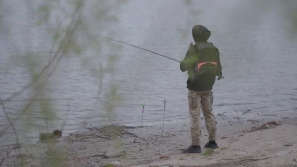 Magabiztos fiatal halász khaki nadrágban kora reggel forgó horgászat a folyóban a város közelében