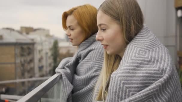 Two caucasian girlfriends covered in blankets standing on the balcony looking away. Two women talking, chatting, gossiping. Meeting of female friends