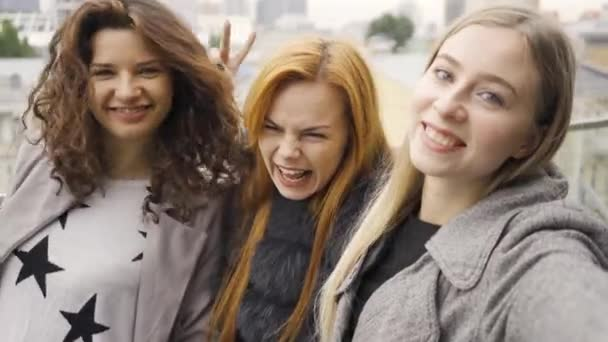 Tři krásné mladé přítelkyně se selfie na letní terase v kavárně