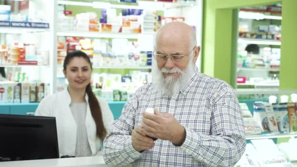 Senior bearded man in glasses examining medication in the pharmacy and smiling to the camera. Pharmacist waiting for the customer to read the label. Healthcare and traditional treatment.
