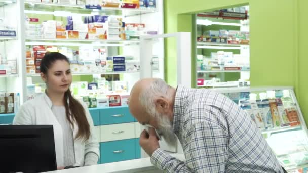 Middle-aged bearded man with runny nose coming to the pharmacy. Young female pharmacist offering the customer medication for the common cold. Buyer examining unknown remedy.