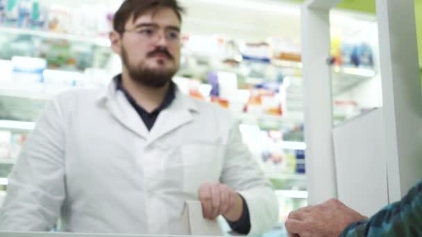 Der junge bärtige Apotheker reicht dem Kunden die weiße Packung mit Medikamenten. Berufstätige in weißer Robe und Brille verkaufen effiziente Medikamente an den Kunden. Gesundheitskonzept.