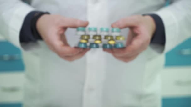 Close-up of male hands showing colorful pills to the camera. Man in white robe offering choice between different types of medications. Pharmacy worker at his workplace.