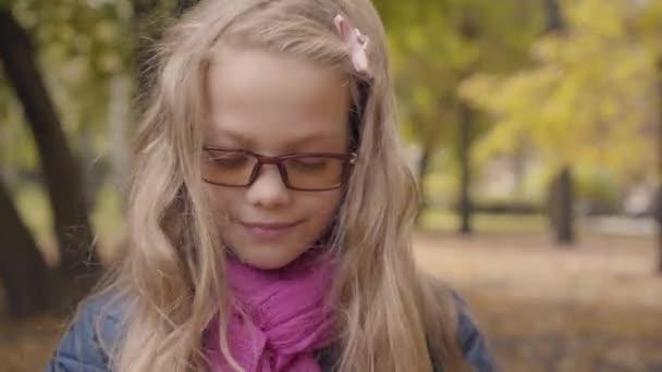 Detailní záběr na veselou bělošku, jak mrká do kamery a usmívá se. Mladá školačka ve fotochromických brýlích a růžové šále pózující v podzimním parku nebo lese