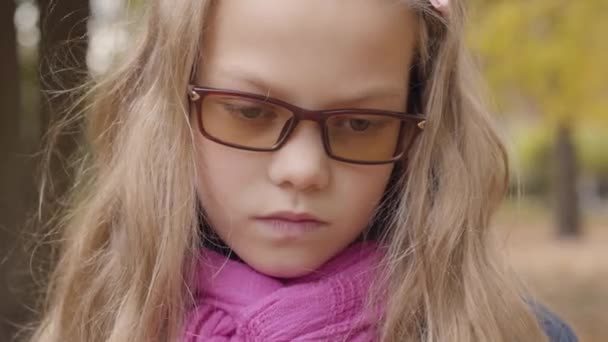 Close-up portrait of a sad Caucasian teenage girl standing in the autumn park and looking at the camera. Young schoolgirl in photochromic glasses and pink scarf displeased with her free time outdoors.