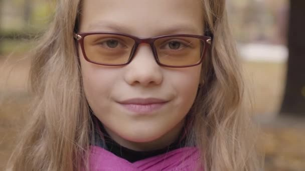 Close-up portrait of a shy Caucasian teenage girl looking at the camera and smiling. Young schoolgirl in photochromic glasses and pink scarf posing in the autumn park or forest