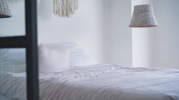 Slowmo z bílých čistých polštářů padajících na postel za slunečního světla. Ráno zpomalte v ložnici. Odpočinek, relaxace, hotelový pokoj, volný čas.