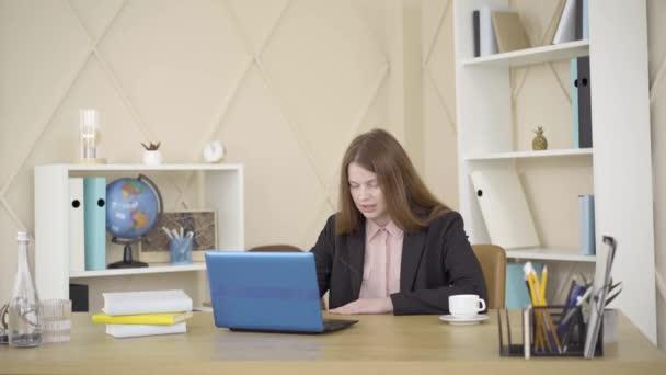 Bezstarostná běloška na volné noze, stojící ve spacích kalhotách a zavírající notebook. Překvapená mladá žena pracující online z domova. Životní styl, práce na dálku, koncept volného času.