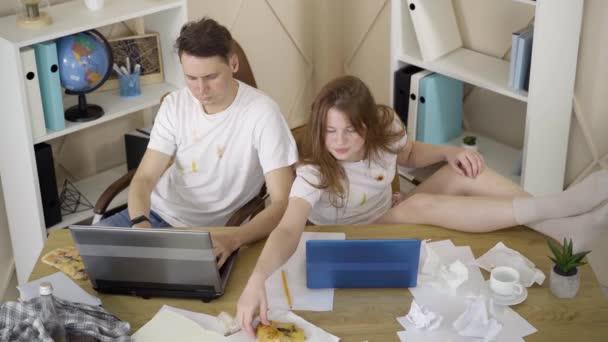 Draufsicht auf junge kaukasische Männer und Frauen in schmutzigen T-Shirts, die mit Pizza sitzen und auf Laptop-Tastaturen tippen. Paar von Freiberuflern, die von zu Hause aus online arbeiten. Lifestyle, freiberufliches Konzept.