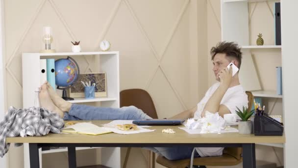 Wide shot of relaxed young brunette man talking on the phone. Portrait of cheerful Caucasian guy sitting at the table with legs on it and chatting. Lifestyle, relaxation, leisure.