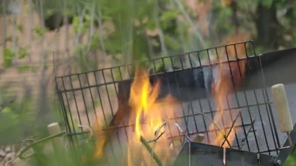 Hořící plamen v grilu zblízka. Hořící oheň venku. Grilování, vaření, víkendové aktivity, párty.
