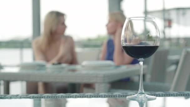 Açık kafedeki masada duran kırmızı şaraplı bardak ve arka planda konuşan iki bulanık sarışın beyaz kadın. Boş zaman kavramı, restoran işi, alkol endüstrisi.