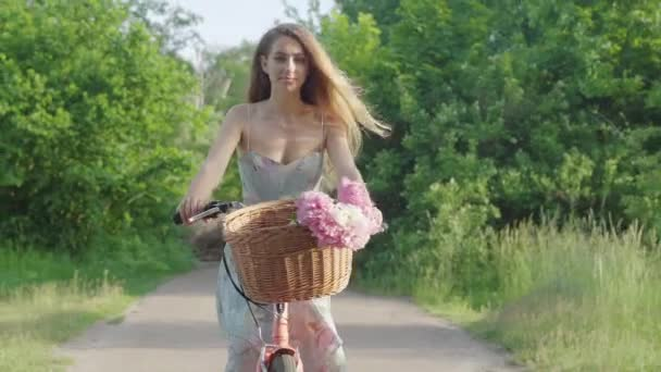 Portrait of attractive young woman riding bike in sunny park and looking away holding hand at forehead. Beautiful Caucasian brunette girl enjoying weekend outdoors. Leisure, resting, relaxation.