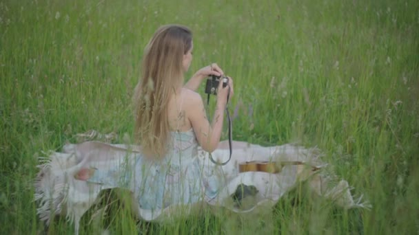 Back view of young brunette lady sitting on green meadow and taking photos on camera. Charming Caucasian woman in retro dress enjoying hobby outdoors on sunny summer day.