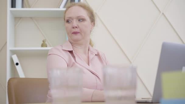 Porträt einer kranken kaukasischen Frau, die eine Flasche mit kaltem Wasser im Gesicht hält. Erschöpfte Seniorin mit Fieber. Medizin, Gesundheitswesen, Covid-19-Pandemie, Coronavirus-Epidemie.