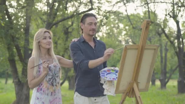 Blond smiling woman admiring man drawing landscape outdoors. Portrait of cheerful beautiful Caucasian wife supporting handsome creative husband painting picture in park. Unity and art concept.