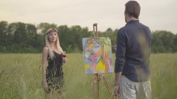 Portrait of beautiful blond woman posing for man drawing picture outdoors at sunset. Confident male artist painting picture on canvas. Loving creative couple resting on meadow.