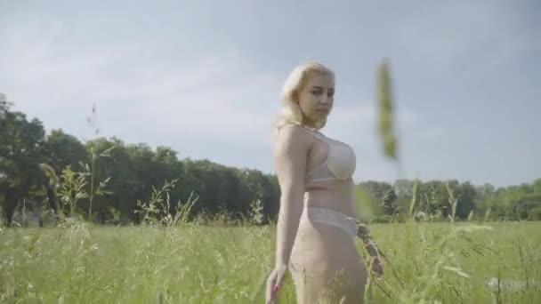 Mitte Aufnahme einer selbstbewussten, dicken Frau in weißer Spitzenunterwäsche, die auf einer sonnigen Wiese im Freien spaziert. Porträt einer sinnlichen übergewichtigen blonden Kaukasierin, die den Sommertag genießt. Körper positiv, Selbstvertrauen.