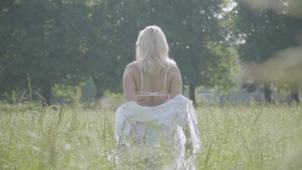 Plumpe junge kaukasische Frau zieht weißes Hemd aus und wendet sich der Kamera zu, die ihren Körper berührt. Porträt einer selbstbewussten Plus-Size-Lady, die an einem sonnigen Sommertag im Freien posiert. Vertrauen und Schönheit.