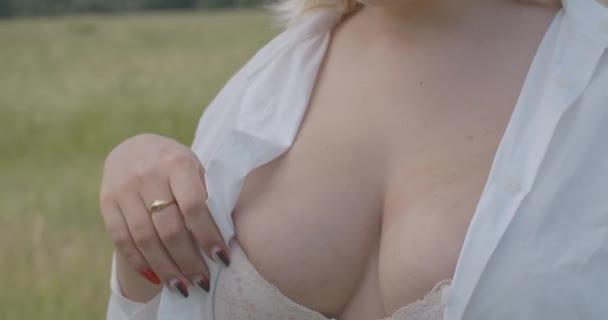 Nahaufnahme einer schönen Plus-Size-Frau, die in die Kamera blickt und ihren Körper im Slowmo sinnlich berührt. Übergewichtige selbstbewusste Kaukasierin posiert draußen in SpitzenbH und weißem Hemd. Cinema 4k ProRes Hauptquartier.