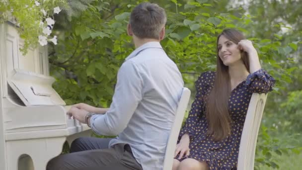Portrait of young beautiful brunette woman admiring mid-adult man playing piano. Happy Caucasian girlfriend listening to music boyfriend plays. Creative romantic couple dating outdoors.