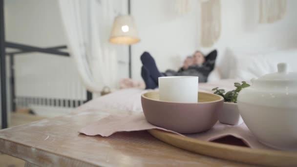 Detailní záběr čaje a svíčky na stole s rozmazaným párem ležícím na posteli v pozadí. Šťastný kavkazský mladý muž a žena odpočívající na Silvestra doma. Vánoční koncept.