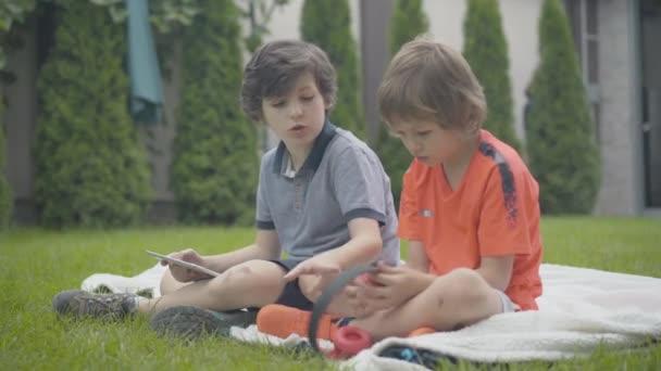 Brünetten Jungen mit Tablet im Gespräch mit niedlichen kleinen Kind mit Kopfhörern. Weitwinkelporträt glücklicher entspannter kaukasischer Kinder, die sich zu Hause auf grünem Rasen ausruhen.