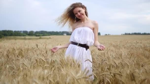 Blondýnka v bílých bohémské šatech na zlatém poli. Koncepce životního stylu.