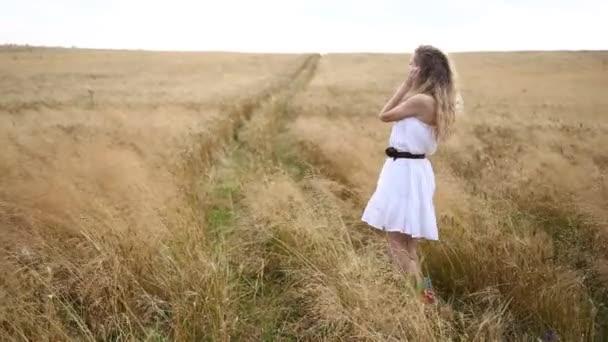 blonde schöne Mädchen im weißen Boho-Kleid auf dem goldenen Weizenfeld. Lifestylekonzept.