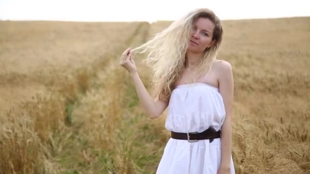Blonde beautiful girl in white boho dress on the golden wheat field. Lifestyle concept.