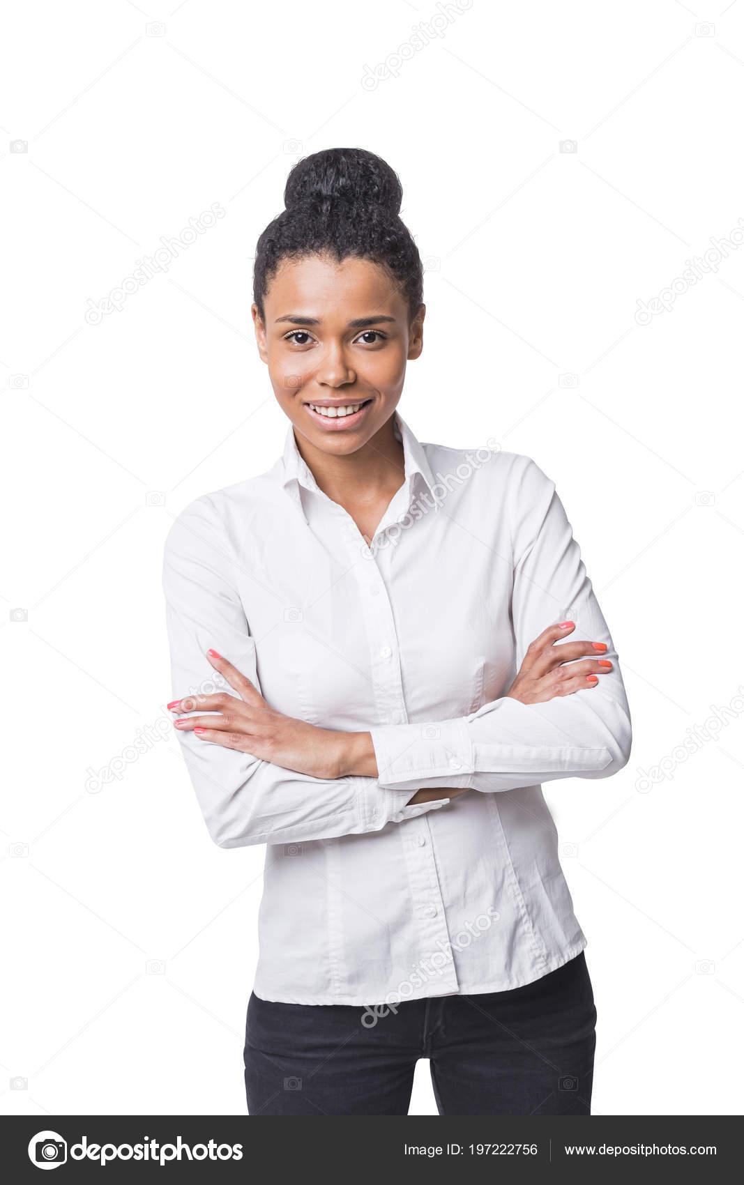 3df090f971 Sorridente giovane donna afro-americana sicura indossando una camicia  bianca e nero pantaloni in piedi con le braccia incrociate e guardando lo  spettatore.