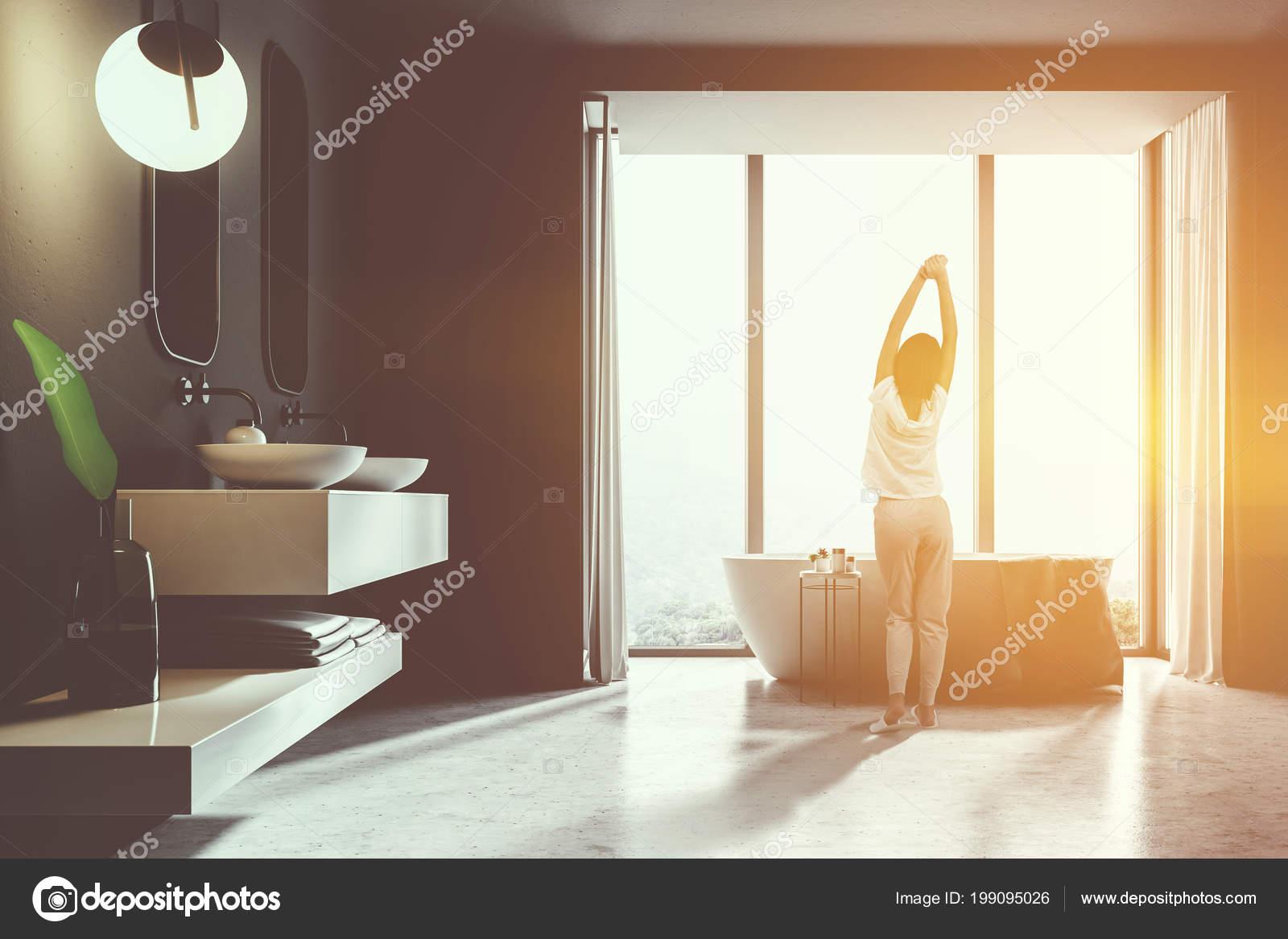 Donna interiore bagno con pareti piastrelle nere doppio lavandino
