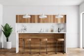 Fotografie Küchenecke mit weißen Wänden, einen hölzernen Fußboden, eine Bar mit Hocker aus Holz und einer Reihe von Lampen über ihm hängen. 3D-Rendering mock-up