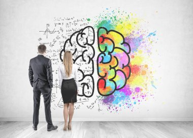 Rear view of young and successful business partners wearing suits looking at a concrete wall with a colorful brain sketch, formula and color splashes. Creativity in business concept