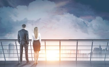 Rear view of young and successful business partners standing on a balcony and looking at a morning city sky with clouds. A rising sun. New beginning concept. Mock up toned image