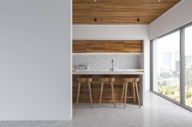 White kitchen interior with a concrete floor, wooden countertops with built in appliances and a wooden bar with stools. A blank wall to the left. 3d rendering mock up