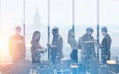 Fotografia Siluette di persone di affari in un ufficio moderno. Uno sfondo di paesaggi urbani di notte e la mattina. Concetto di lavoro di squadra Toned immagine doppia esposizione