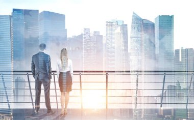 Rear view of young and successful business partners standing on a balcony and looking at sun rising in a modern city. Business success and lifestyle concepts. Mock up toned image double exposure
